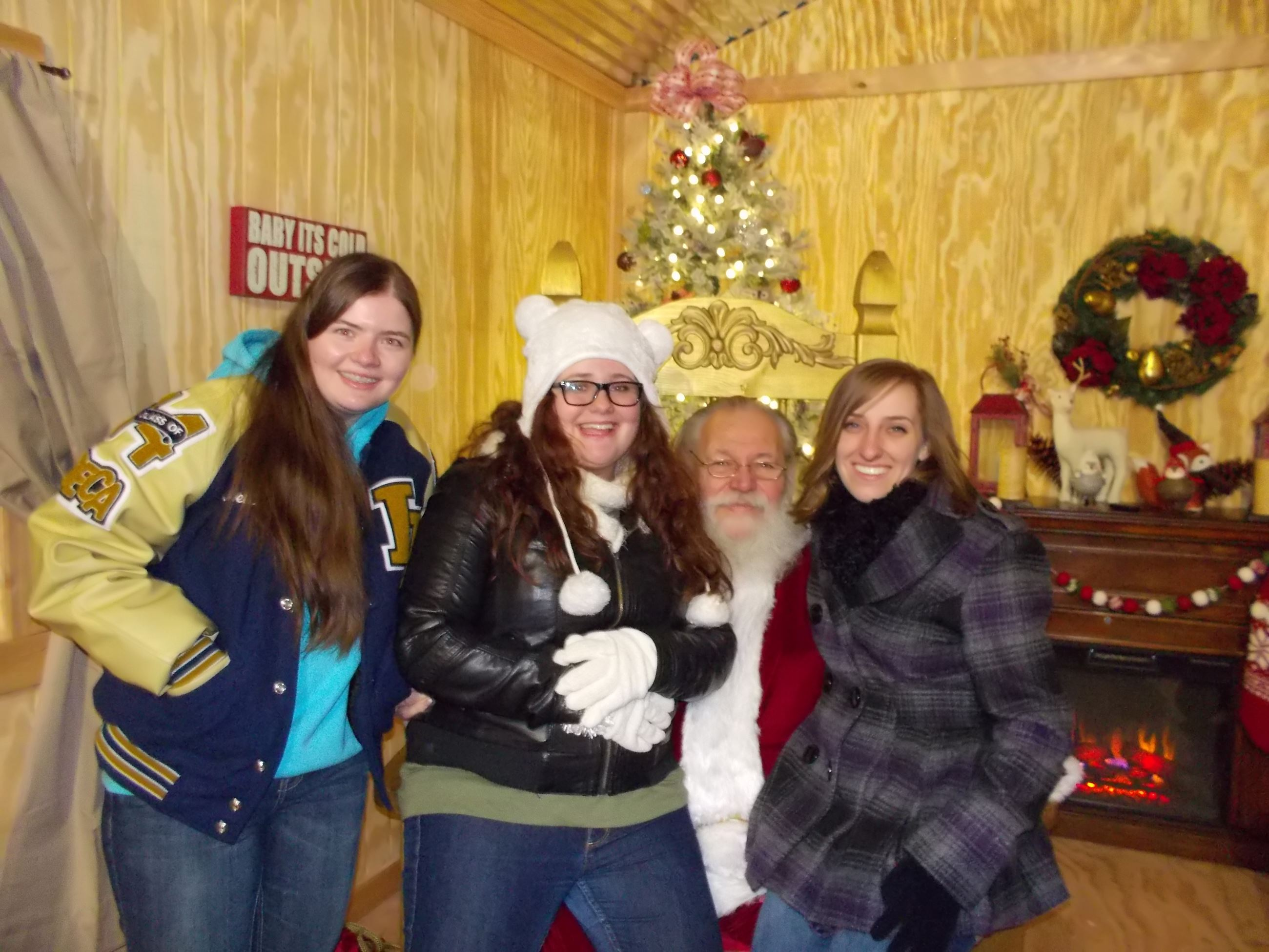 3 young ladies posing with Santa