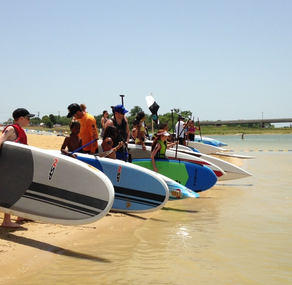People lined up on the beach with their paddle boards